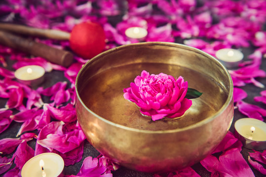 Tibetan singing bowl with floating inside in water purple peony flower. Burning candles, special sticks and petals on the black stone background. Meditation and Relax. Exotic massage. Selective focus.