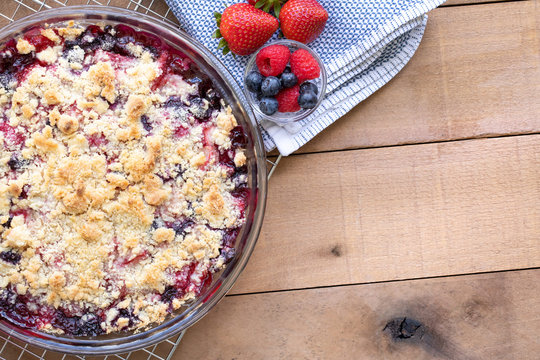 Flat lay of a berry cobbler and spring berries, on a wood table with space for text on the right