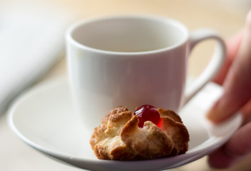 Porcelain white pot with little pastry on the saucer
