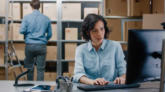 Female Inventory Manager Sitting at Her Desk and Using Personal Computer, Worker Puts Package on the Designated Shelf. In the Background Rows of Cardboard Boxes with Products Ready For Shipment.
