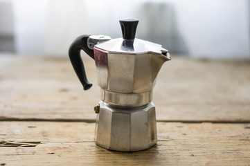Isolated espresso coffee maker called moka on a wooden rustic table in the kitchen