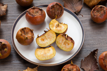 Close up of medlar fruit on a plate and cut in half