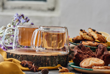 two glass cups of tea on a wooden saw, with cookies and dried flowers on the background. wooden background. autumn tea composition. close-up