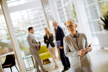 Portrait of senior businesswoman with digital tablet while other business people standing in background