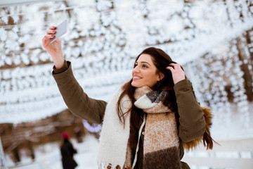 Young woman in winter clothes taking selfie by smartphone outdoors