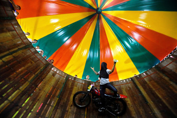 "A stuntman covering his face rides a motorcycle inside the ""Well of Death"" attraction during a fair in Bangkok"