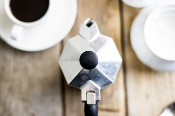 Espresso coffee maker from the top on the wooden background with porcelain cup and sugar-bowl on a side