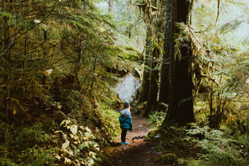 Young girl standing in the middle of a forest