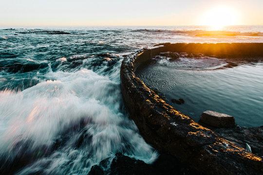 Ocean waves crashing against barrier at sunset