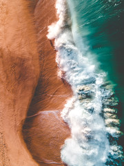 Aerial view of waves crashing along the shore