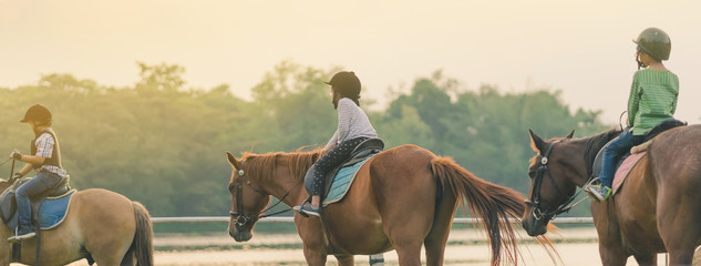 Photo sur cadre textile Chevaux Kids learn to ride a horse near the river before sunset.