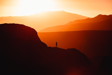 Silhouette of person standing on mountain during sunset