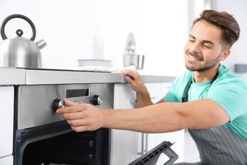 Young man baking something in oven at home