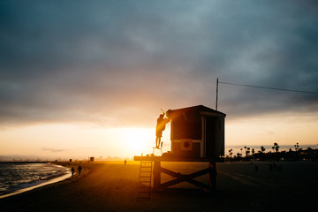 Person fixing a lifeguard hut during sunset on a beach