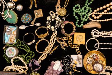 Golden vintage colorful jewelery on black velvet.