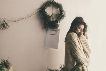 Stylish hipster girl in knitted sweater posing in rustic room on background of handmade christmas wreath and lights. Atmospheric cozy moments, winter holidays. Moody image