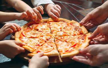 Hands taking pizza slices from wooden table, close up view.