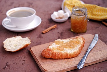 Breakfast: a cup of coffee, fresh croissant on a wooden board, smeared with orange jam.