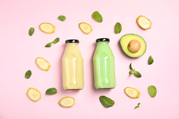 Flat lay composition with different smoothies in bottles and ingredients on color background
