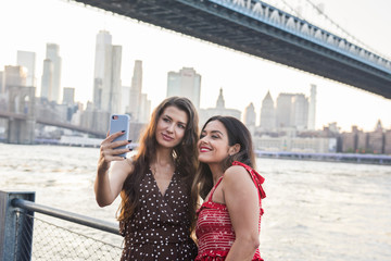 Two women taking a selfie by the Manhattan Bridge