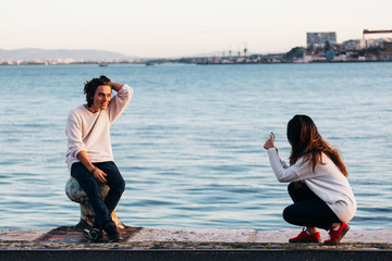 woman taking photo on smartphone of young man near water