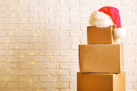 Blank brown freight box with Santa Claus hat on top, brick wall with Christmas lights on background. Moving company / delivery service holiday deals promotion concept. Copy space, close up.