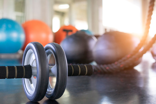 Close up of a fitness equipment in gym. Exercise wheel in a gym. Fitness roller equipment. Selective focus.