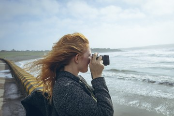 Side view of woman taking picture with camera on beach
