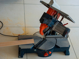 Circular saw and timber strip on table in carpenter's workshop