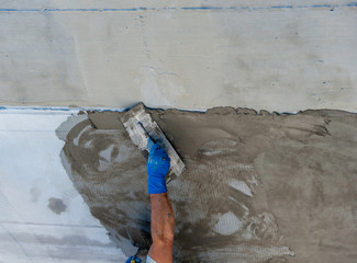 Hand using trowel on fresh concrete in construction site