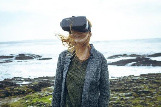 Redhead woman using virtual reality headset on beach
