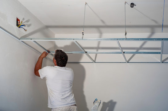 Construction worker assemble a suspended ceiling with drywall and fixing the drywall to the ceiling metal frame with screwdriver.