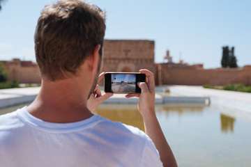 Man with mobile phone at El Badi Palace in Morocco