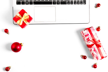 Online shopping for winter holidays concept. Flat lay composition with white laptop, black keyboard and traditional festive Christmas decoration. Close up, copy space, background, top view.