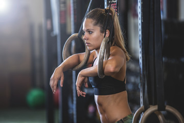 Woman exercising with gymnastic rings in sports hall
