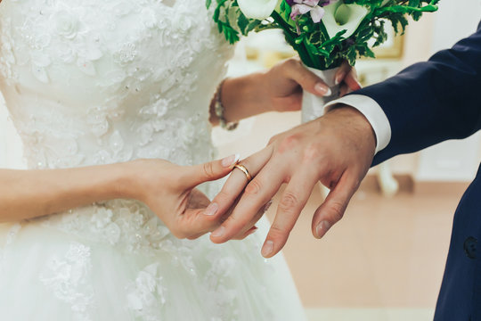 The bride wears a ring to the groom at the wedding ceremony