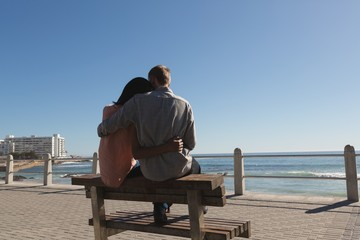 Couple sitting on bench near beach