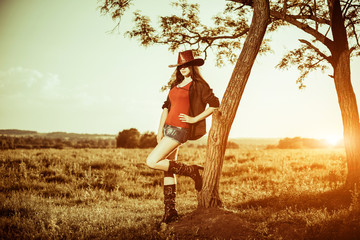 pretty cowgirl in hat and shirts leaning to tree at rural sunset landscape