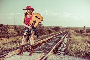 lovely brunet in hat with guitar at rural railways