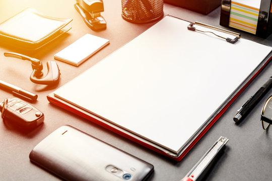 office desk with mock-up paper, eyeglass, pen, smartphone, key, wallet, agenda, cactus, stapler, Bluetooth audio headset