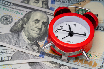 concept of time value. Cool alarm clock on US dollars.