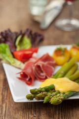 grüner Spargel mit Sauce Hollandaise auf einem Teller