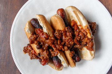 row of chili dogs in buns flat lay on wood table