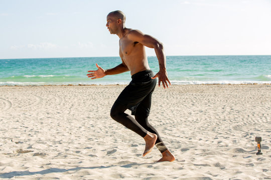 Young man running on the Miami beach