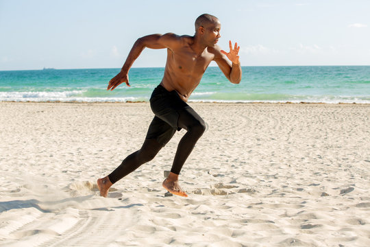 Young man running on the beach