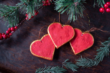 hand painted Christmas red and gold heart ornaments with copy space on festive wood table