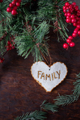 hand painted Christmas heart ornament with word family on festive wood table