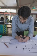 Male executive using mobile phone while working on blueprint