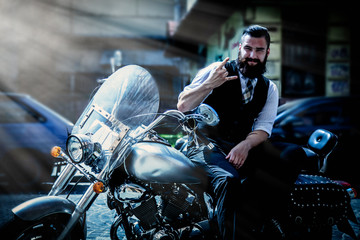 Serious bearded biker man in black jacket sitting on motorbike as symbol of travel and adventure.