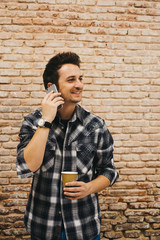 Young man with cup talking on smartphone
